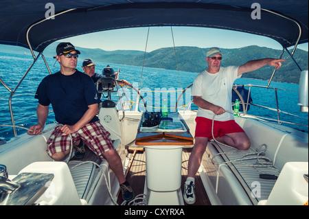 Drei Männer der Besatzung am Heck einer Yacht segeln abseits die kroatische Küste, Kroatien, Europa - Stockfoto