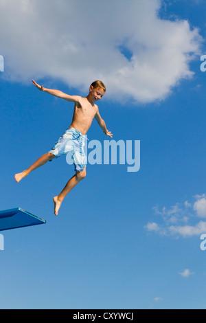 Junge, springen vom 3-Meter-Sprungbrett am Außenpool - Stockfoto