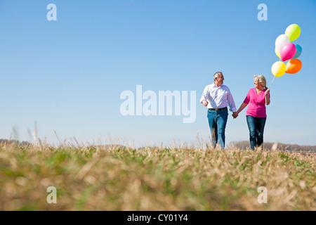 Paar mittleren Alters lachend, als sie über eine Wiese mit bunten Luftballons in den Händen gehen - Stockfoto
