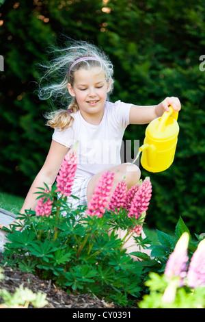 Mädchen mit einer Gießkanne im Garten - Stockfoto