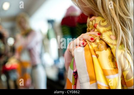 Junge Frau, die versucht auf Kleidung in einem Mode-shop - Stockfoto