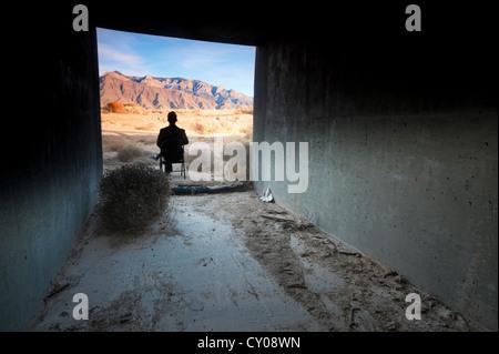 Silhouette der männlichen Figur sitzt im Tunnel in Wüste - Stockfoto