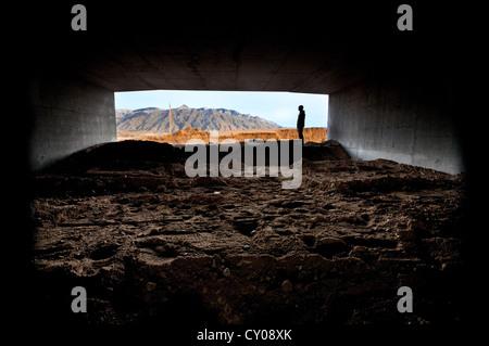 Silhouette der männlichen Figur stehend im Tunnel in Wüste - Stockfoto