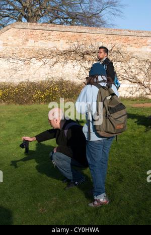 Mann nach unten um zu fotografieren mit anderen Menschen stand neben ihm hocken - Stockfoto