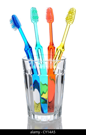 Vier multi-rosafarbig-Zahnbürsten in ein Glas Wasser stehen. Hochformat über einen weißen Hintergrund mit Reflexion. - Stockfoto