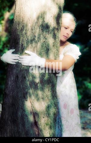 eine Frau in einem geblümten Kleid ist einen Baum umarmen. - Stockfoto