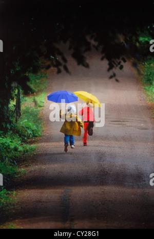 Jungen und Mädchen laufen auf Landstraße in den Regen halten bunte Sonnenschirme - Stockfoto
