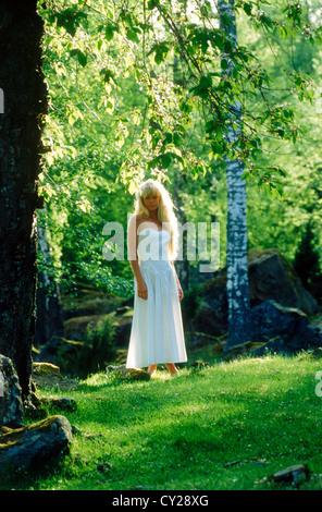 Schwedische Frau mit blonden Haaren in weißen Sommer Kleid barfuß im Birkenwald - Stockfoto
