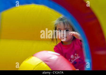 Glückliches Kind Mädchen springt auf den Hüpfburg-aufblasbare Jumper ein Kinderspielplatz. - Stockfoto