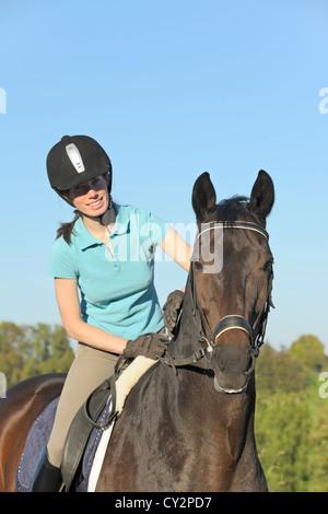 Glücklich junge Reiter auf der Rückseite ein Hannoveraner Pferd - Stockfoto