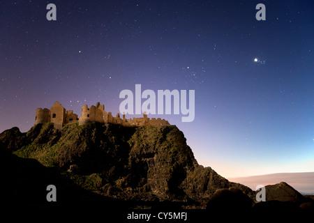 Dunluce Castle gefangen in der Nacht im Mondlicht. - Stockfoto
