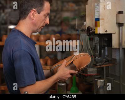 erwachsener Mann arbeitet in einer Schuhfabrik, Überprüfung der Qualität der Produkte - Stockfoto