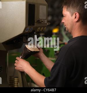 erwachsener Mann arbeitet in einer Schuhfabrik, die Sohlen der Schuhe, an einer Maschine Nähen - Stockfoto