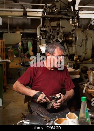 erwachsener Mann arbeitet in einer Schuhfabrik, die Sohlen der Schuhe manuell einfügen - Stockfoto