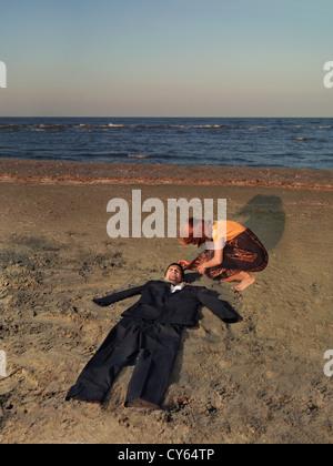 jungen Geschäftsmann gestrandet am Ufer des Meeres, mit einem empty-Suit wo sein Körper sein sollte, und eine junge - Stockfoto