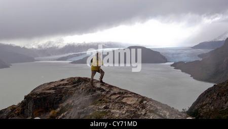 Ein Abenteurer, stehend auf einem Gipfel über einen Gletscher in Patagonien, Chile. - Stockfoto