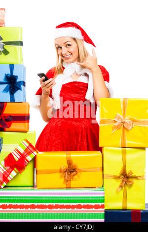 Glückliche Mädchen Weihnachten Santa Kostüm mit Handy, umgeben von Geschenk-Boxen, isoliert auf weißem Hintergrund. - Stockfoto