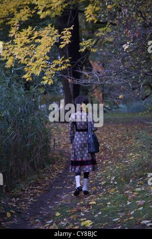 Junge Frau geht allein durch das Herbstlaub im Prospect Park, Brooklyn, NY. - Stockfoto