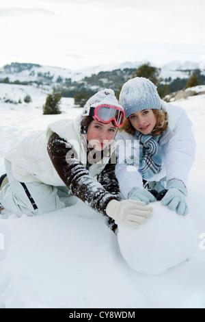 Mädchen im Teenageralter rollenden Schneeball zusammen, portrait - Stockfoto