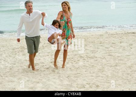 Eltern, die junge Tochter zu schwingen, wie sie am Strand Fuß - Stockfoto