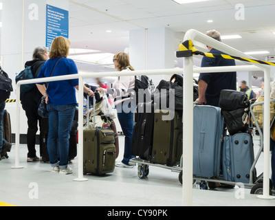 Menschen im Einklang mit Gepäck warten - Stockfoto