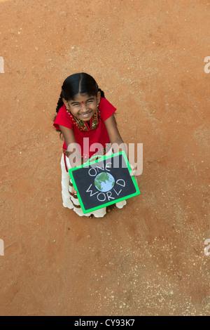 Indianerdorf Mädchen mit ONE WORLD geschrieben auf einer Tafel in einem indischen Dorf. Andhra Pradesh, Indien - Stockfoto