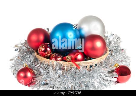 Haufen von Weihnachtskugeln in einem Korb auf einem weißen Hintergrund - Stockfoto