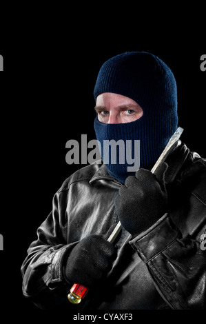 Ein krimineller Dieb in eine Sturmhaube, seine Identität zu verbergen hält einen großen Schraubendreher, wie er - Stockfoto