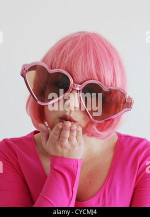 junge Frau, liebevoll, rosa Brille, Schlag einen Kuss - Stockfoto