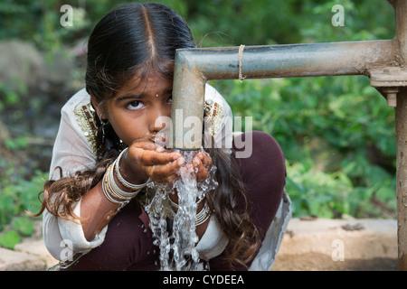 Indische Mädchen trinken aus einer Hand-Wasserpumpe in einem indischen Dorf. Andhra Pradesh, Indien - Stockfoto