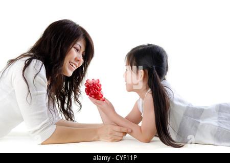 Mutter und Tochter teilen Trauben auf weißem Hintergrund - Stockfoto
