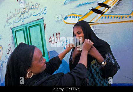 Ägypten. Assuan. Frauen des nubischen Stammes in traditioneller Kleidung vor Dekorationen an der Wand. - Stockfoto