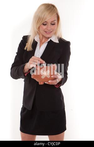 Frau betrachtet die fehlerhaften Zustand ihrer Finanzen, wie sie eine einzelne Münze in ein Sparschwein mit einem - Stockfoto