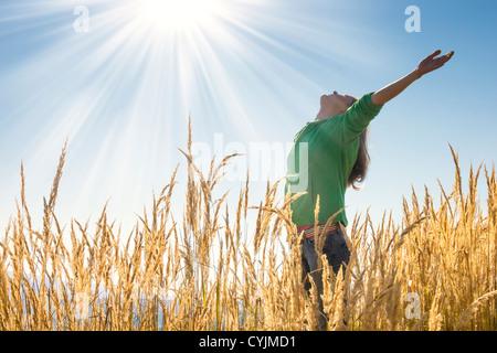Fröhliches junges Mädchen, hob die Arme mit Glückseligkeit und Freude in dem hohen Rasen an einem schönen sonnigen - Stockfoto