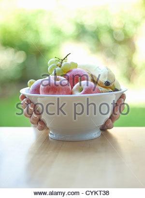 Hände halten Obstschale - Stockfoto