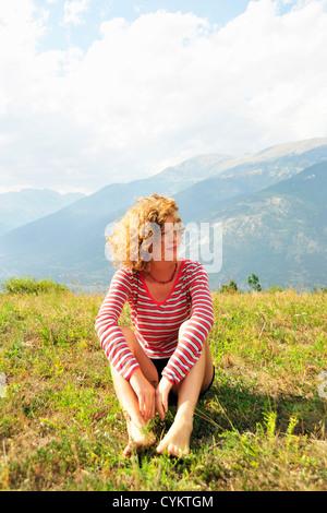Frau sitzt auf ländlichen Hügel - Stockfoto