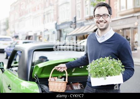 Mann laden produzieren in Auto - Stockfoto