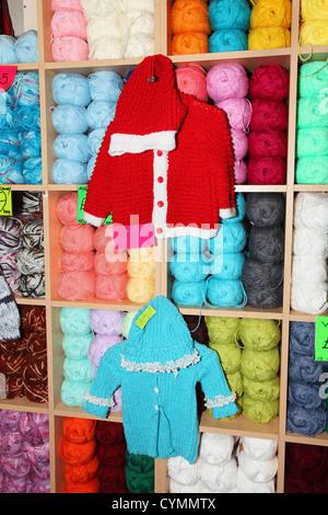 Gestrickte Baby-Kleidung und Kugeln aus Wolle in Regalen - Stockfoto