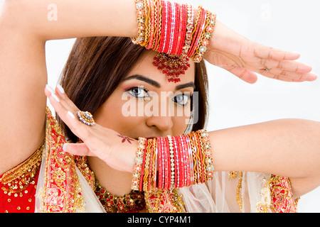 Schöne Gesicht einer bengalischen Braut mit ihren Armen über dem Kopf bedeckt mit bunten Armbänder, isoliert - Stockfoto