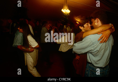 Paare Schmusen und kuscheln während einer late-Night Party, wenn die Lichter niedrig sind und die Stimmung intim - Stockfoto