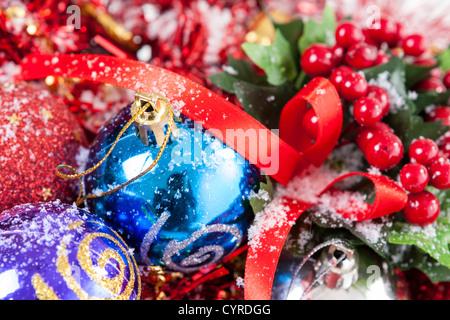 Schöne Weihnachtsarrangement mit bunten Kugeln und Holly Beeren mit Schnee bedeckt. - Stockfoto