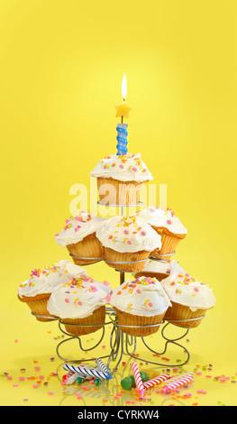 Cupcakes auf mehreren Ebenen Stand mit Kerze auf gelbem Hintergrund - Stockfoto