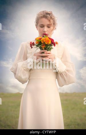 eine Frau in einem viktorianischen Kleid auf einer Wiese mit einem Blumenstrauß - Stockfoto