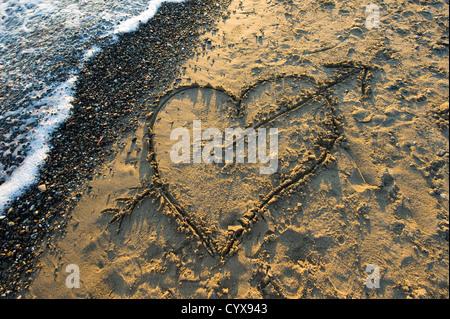 Ein Herz mit einem Pfeil an einem Strand in Sand gezeichnet - Stockfoto