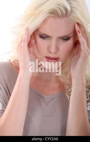 Blonde Frau, die unter Kopfschmerzen leiden - Stockfoto