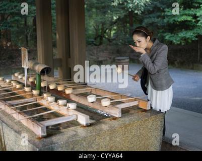 Schöne junge Japanerin Meiji-Jingu Schrein, Tokyo zu besuchen. Bei der Reinigung Trog (Chōzuya oder Temizuya) Besucher - Stockfoto