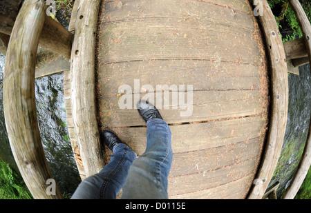 Blick auf Füße nach unten auf eine hölzerne Fußgängerbrücke stehende person - Stockfoto