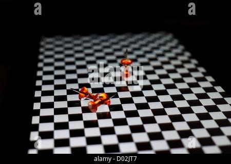Orange Reißnägel auf karierten Oberfläche - Stockfoto