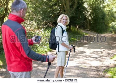 Ein älteres paar zu Fuß entlang einem Feldweg, navigieren mit dem smartphone - Stockfoto