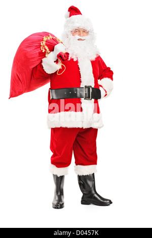 In voller Länge Portrait von Weihnachtsmann hält eine Tasche voller Geschenke auf seinem Rücken isoliert auf weißem - Stockfoto